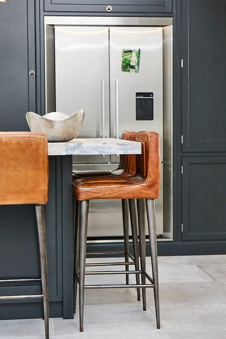 Leather and metal bar stool under bespoke kitchen island painted dark black with reclaimed worktop