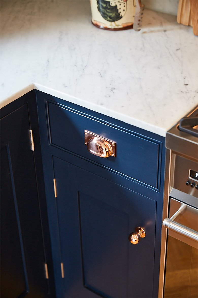 Copper cup handle and copper hinge on dark blue painted bespoke kitchen cabinet
