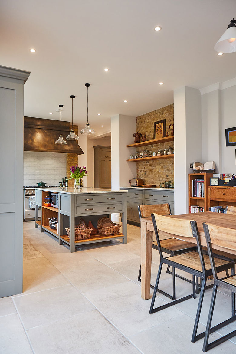 Dining chair in open plan kitchen with yellow London brick and solid oak shelves