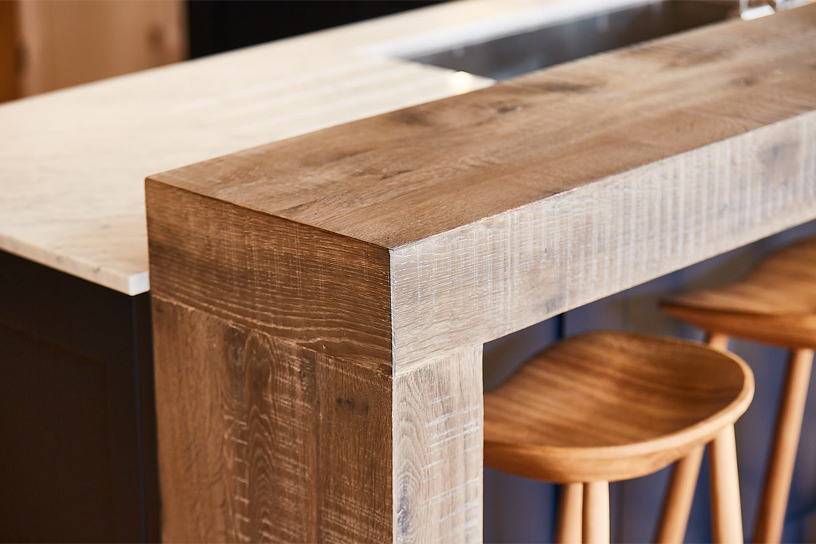 Rustic wood breakfast bar with solid oak bar stools and blue back panel