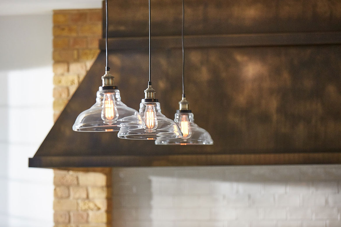Three delicate glass pendant lights with aged brass canopy in background
