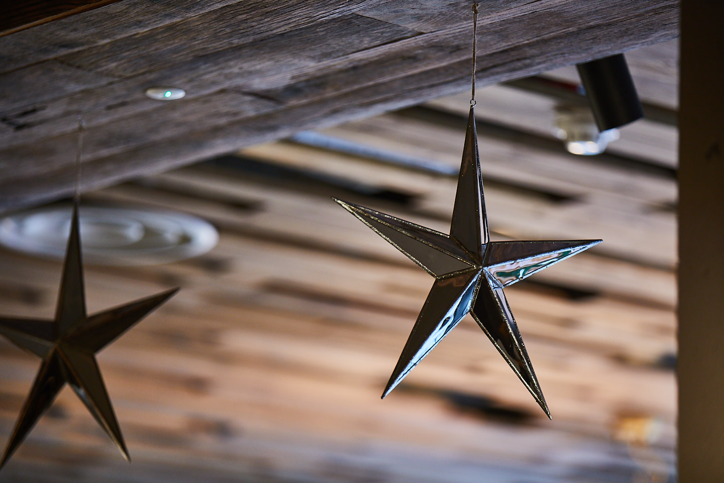Metal star hangs from wood cladded ceiling