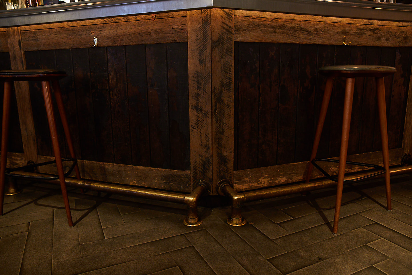 Rustic bar with oak stools and brass foot rail