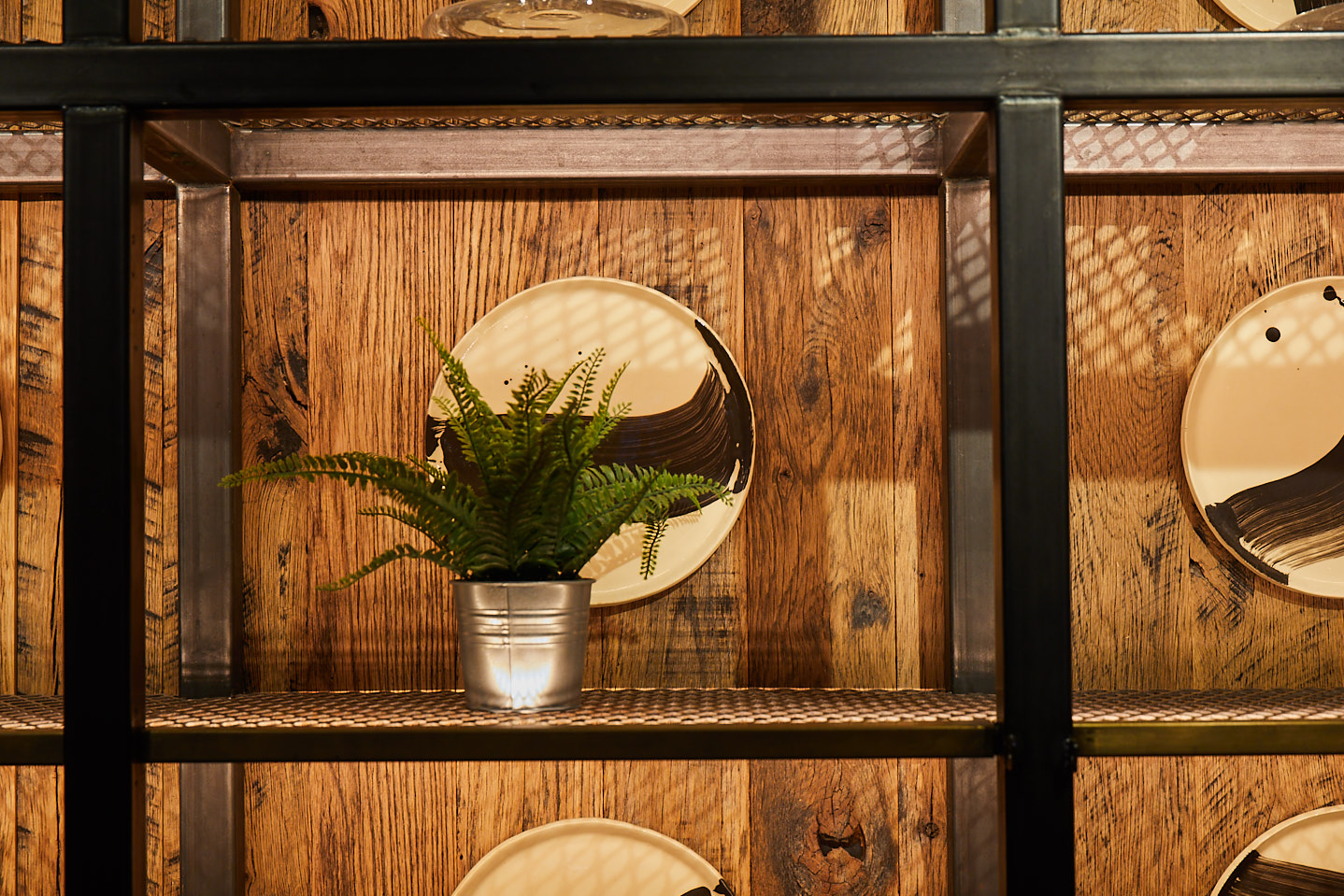 Plant sat on industrial metal shelves with reclaimed timber wall and mirror hung behind