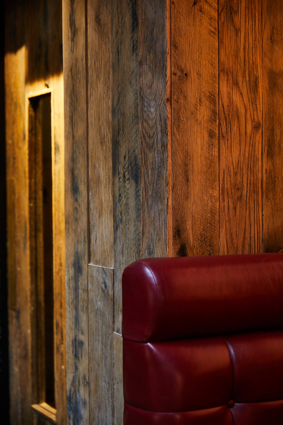 Red leather backrest contrasts against rustic timber wood wall