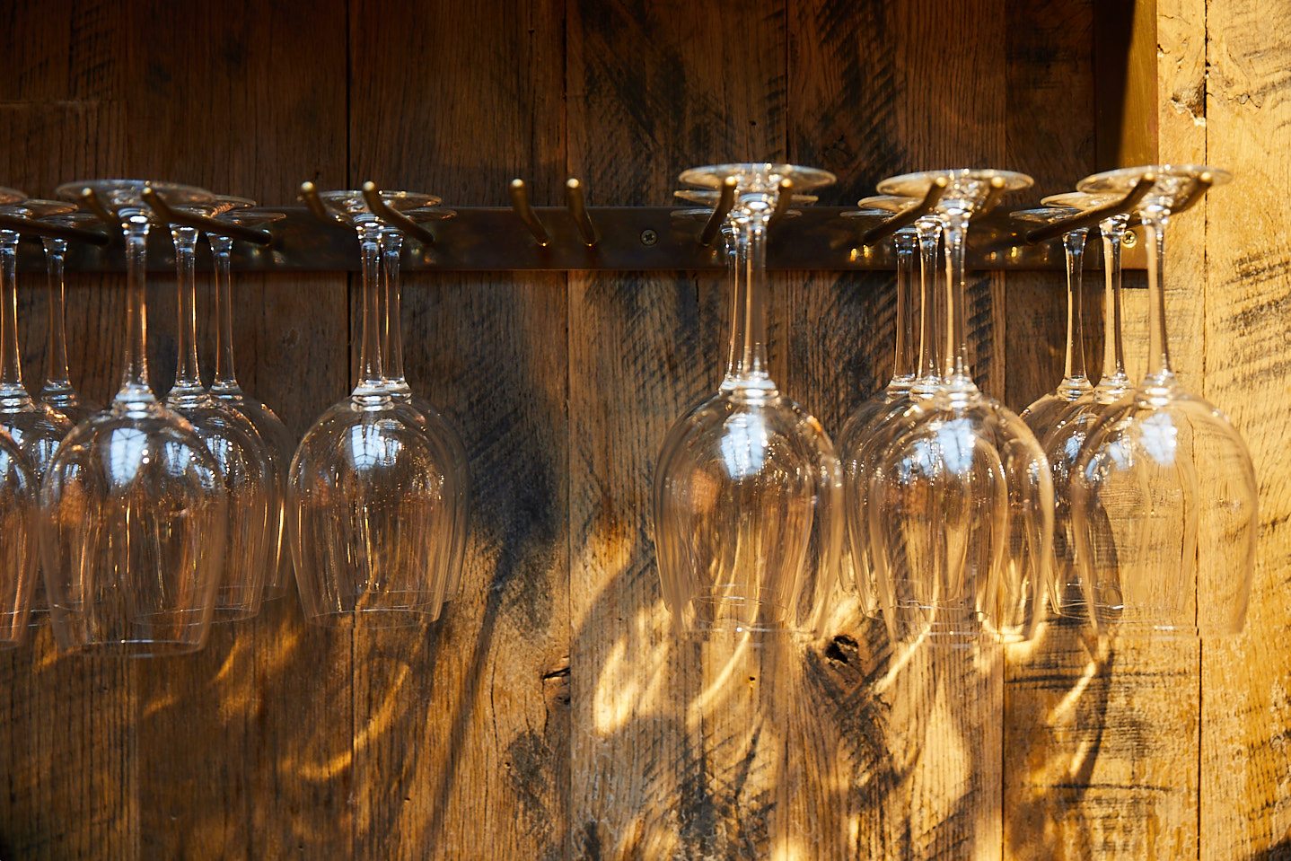 Wine glasses hang from metal rails with reclaimed clad wall