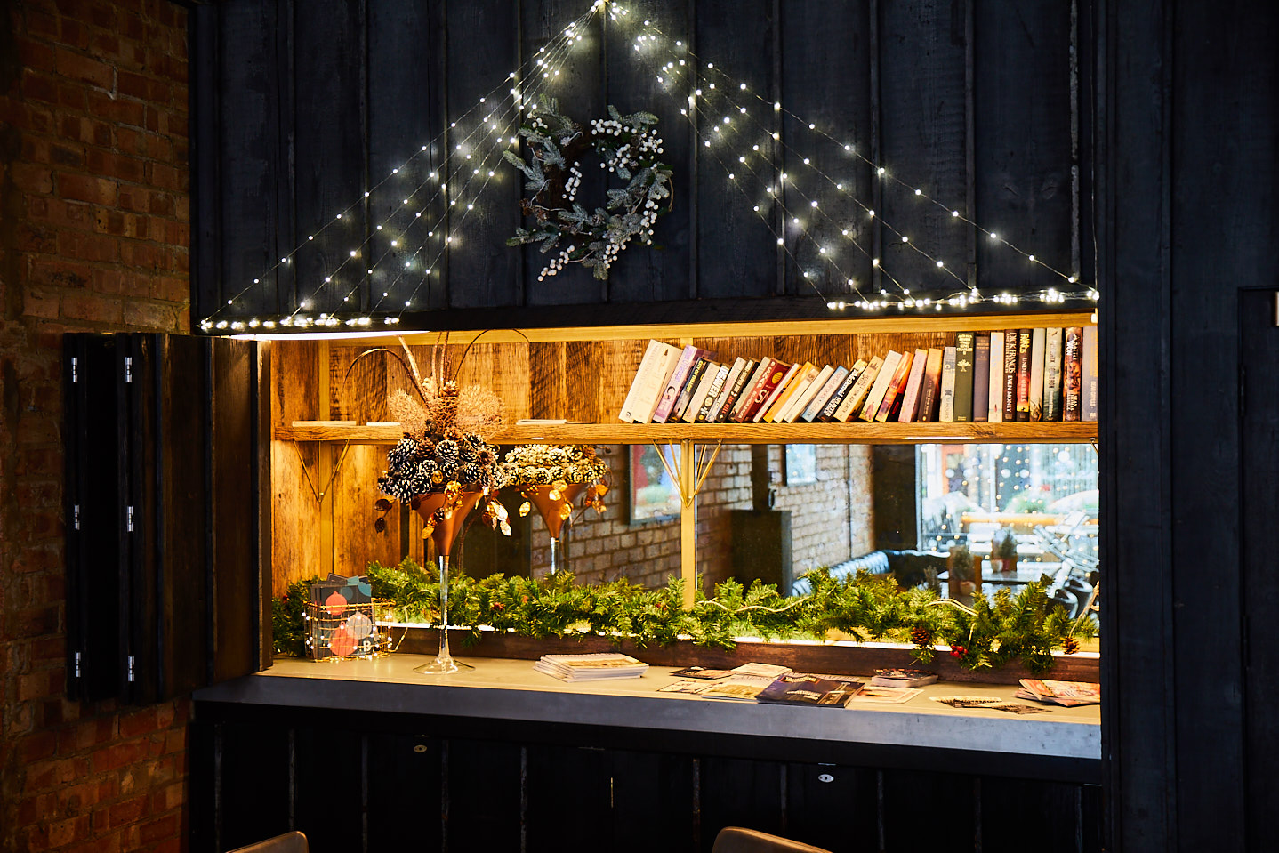 Dark blue pained cladding surrounds feature cabinet with cocktail glass and books