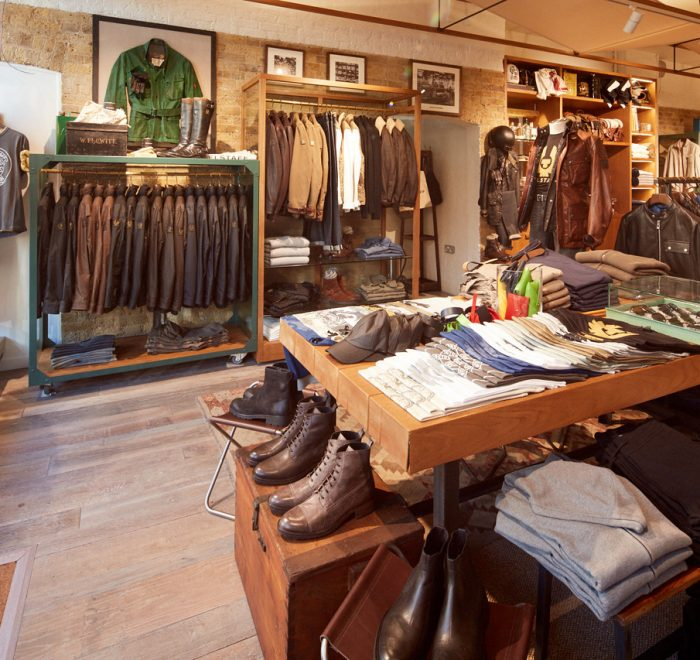 Clothes shop interior with rustic wood floor exposed brick displaying shoes and leather jackets