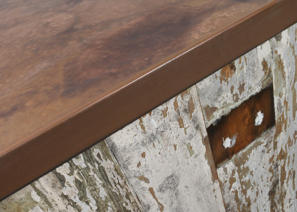 Distressed copper worktop on reclaimed wood cladding