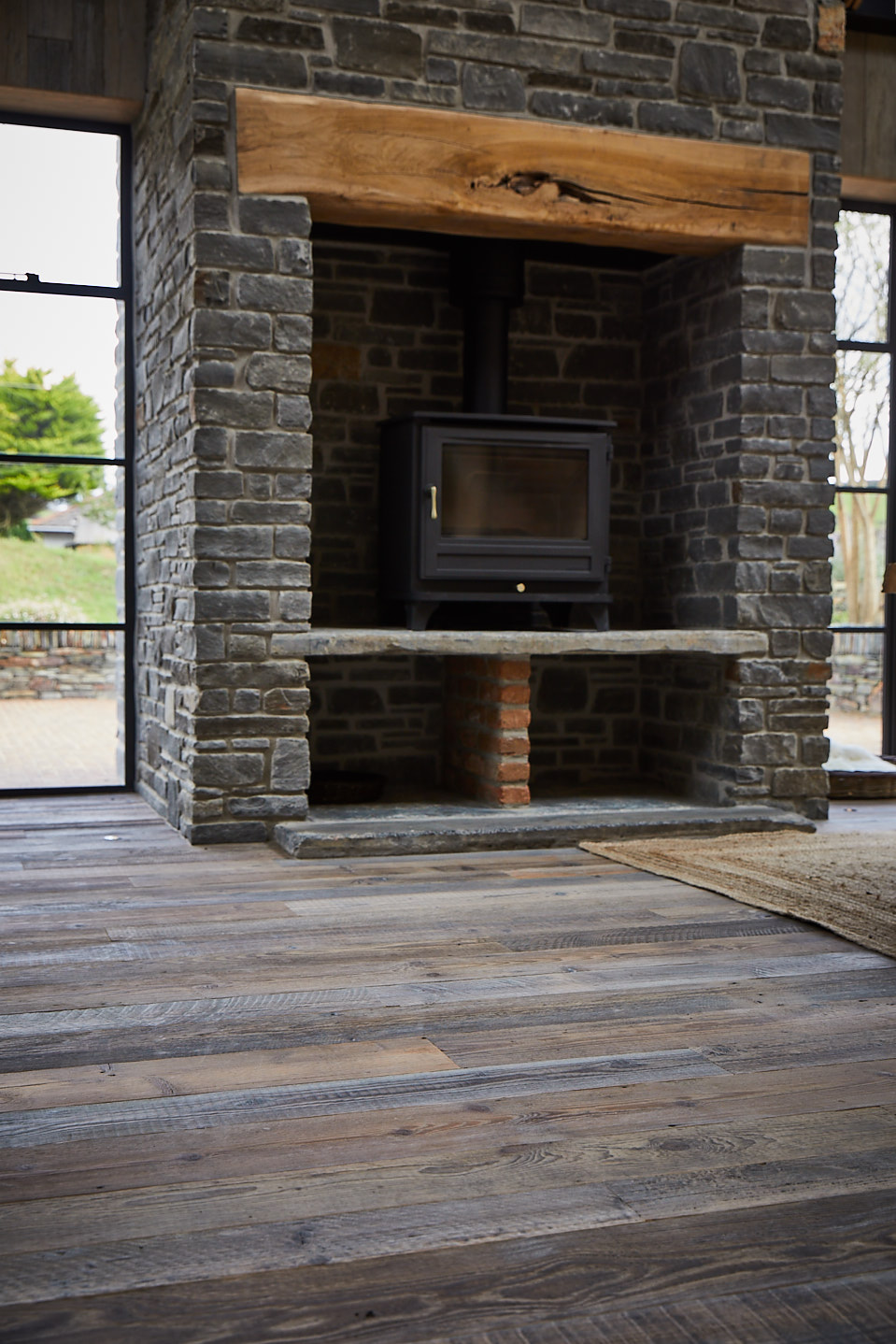 Reclaimed pine floor boards and large stone fireplace