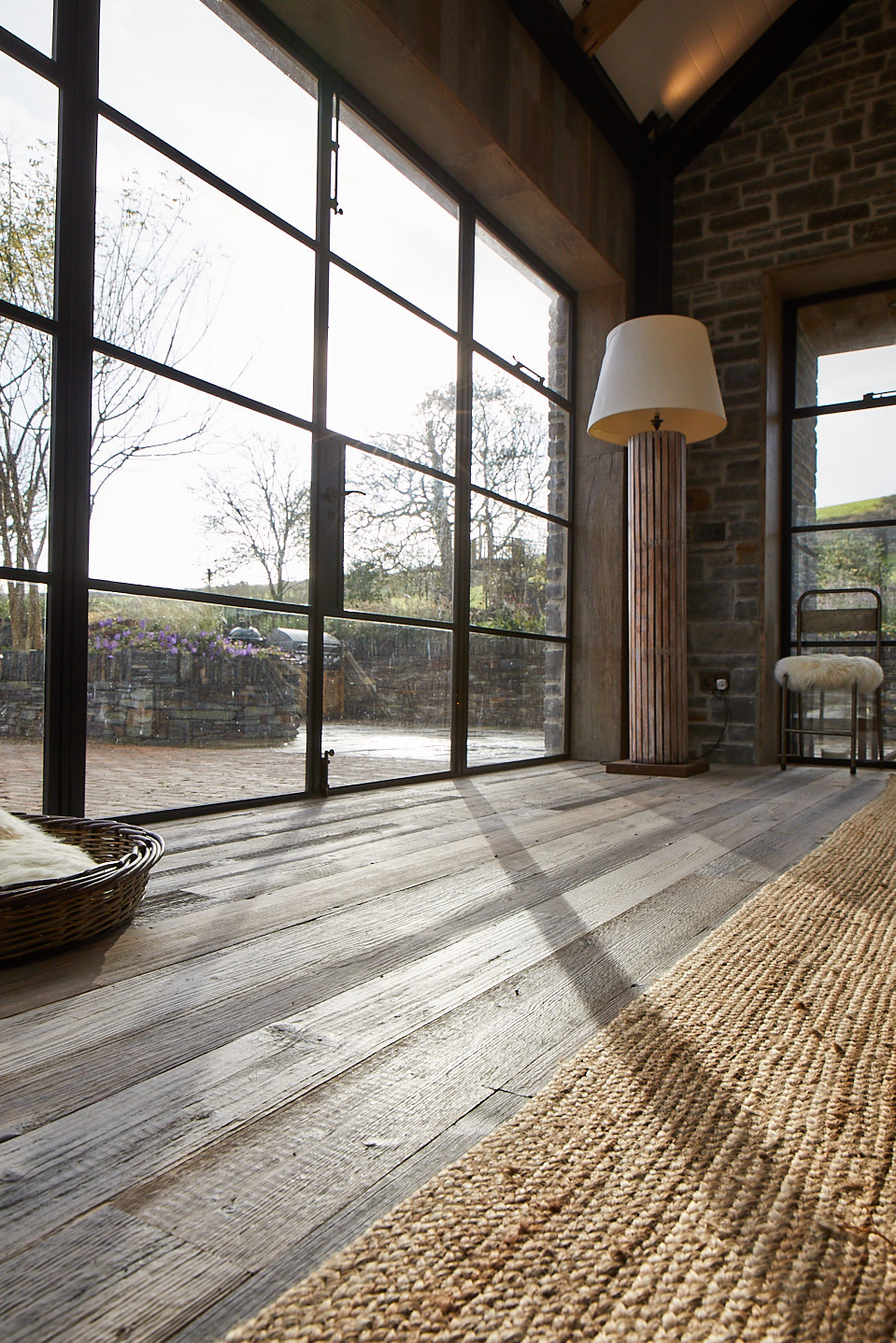 Shadow of crittall door shines across reclaimed wood floor boards and rustic rug