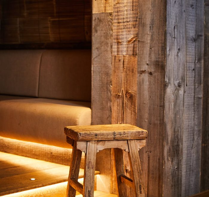 Stool made from reclaimed oak with rustic oak backdrop