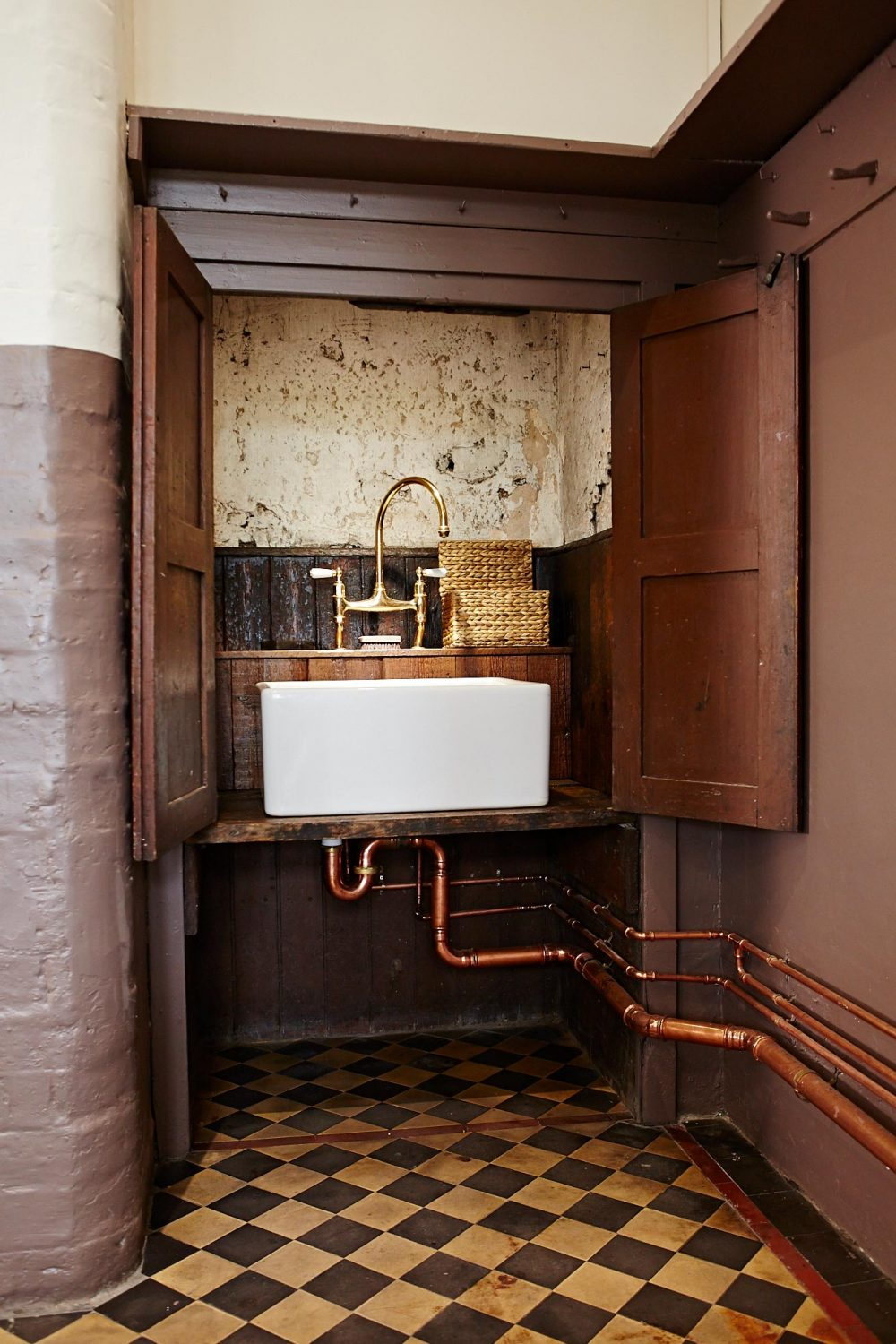 Shaws ceramic sink in original cupboard with exposed copper pipes and brass mixer tap