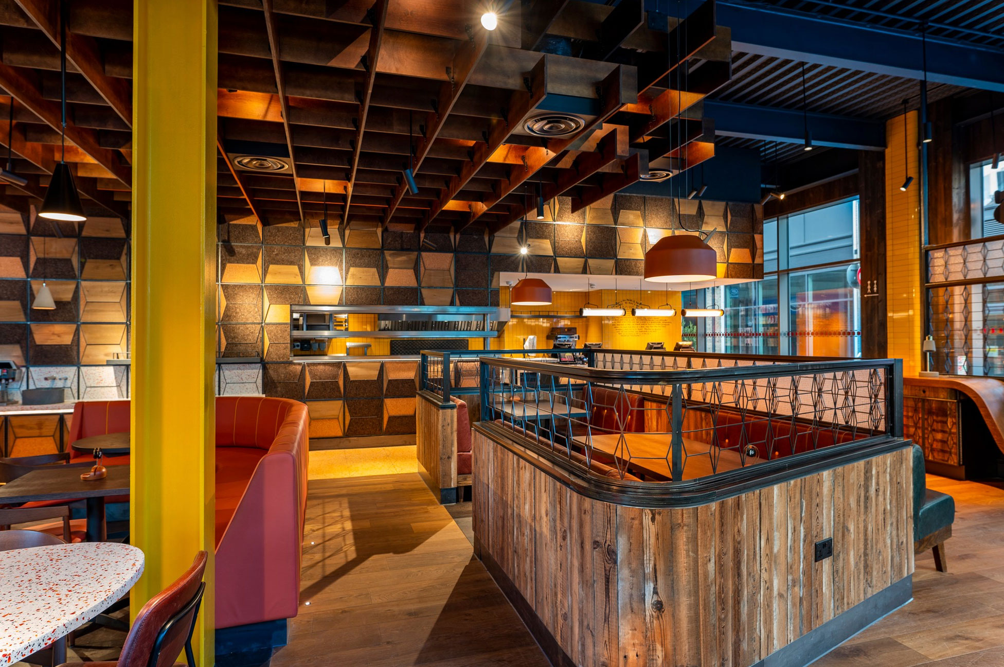 Rustic wood curved around seating area in Nando's with bright yellow RSJ