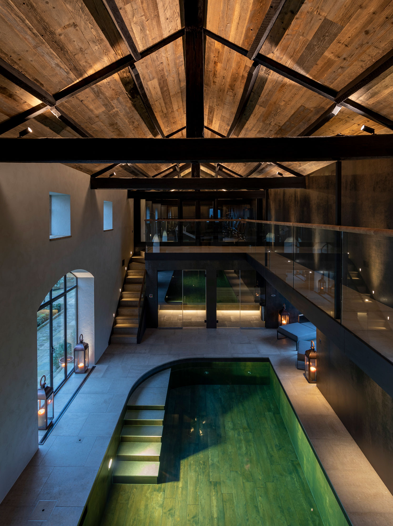 Swimming pool with wooden floor and exposed RSJ beams above
