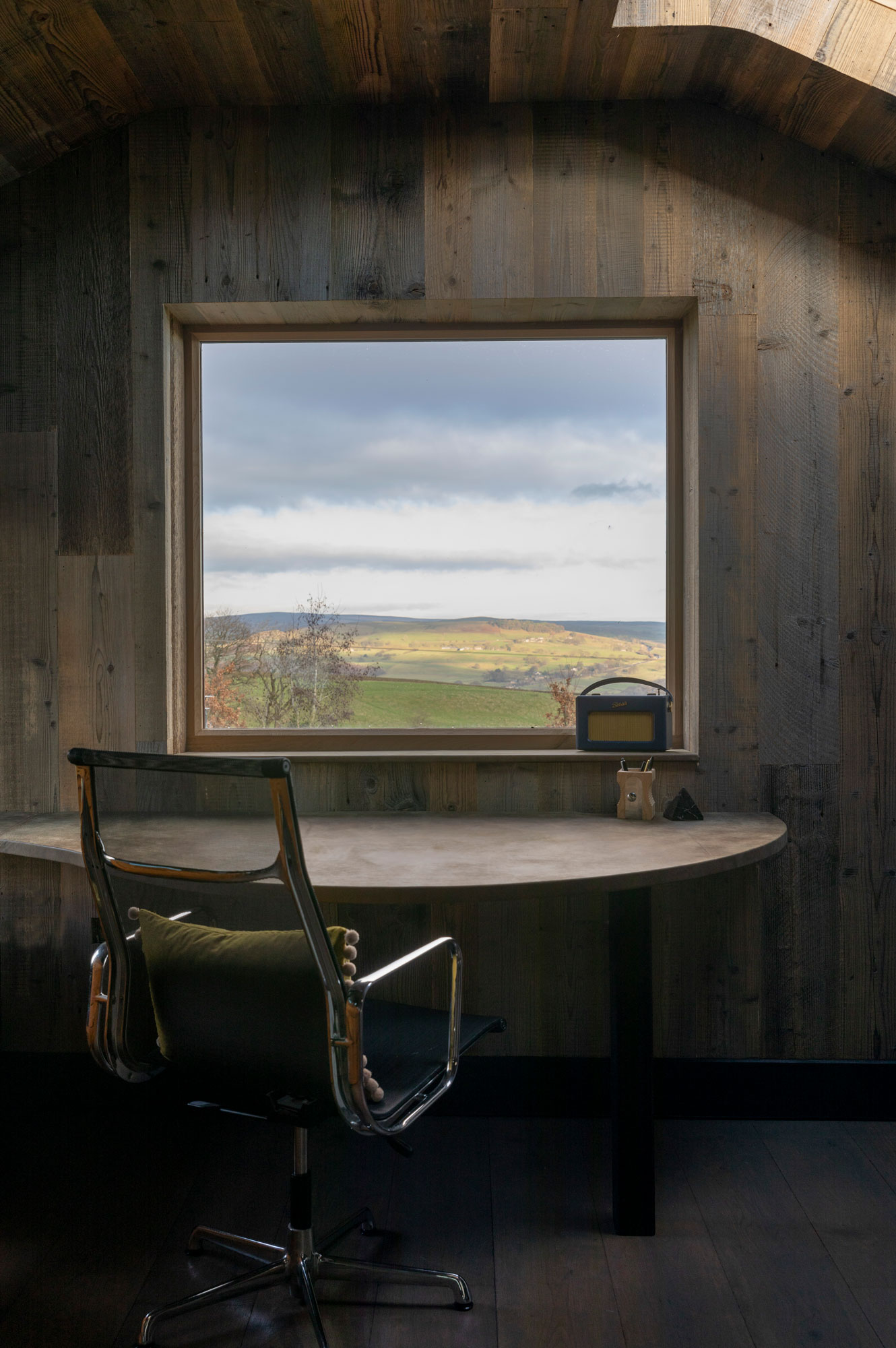 Office desk and chair in front of window in a fully cladded wood room