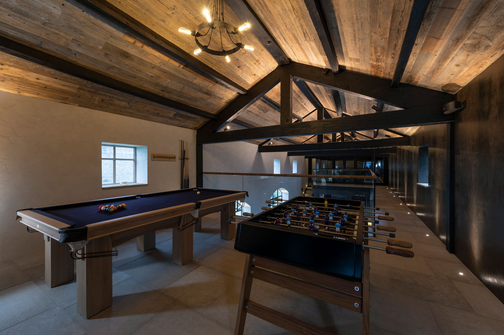Pool table and foosball table in large room with tiled floor on wood clad ceiling