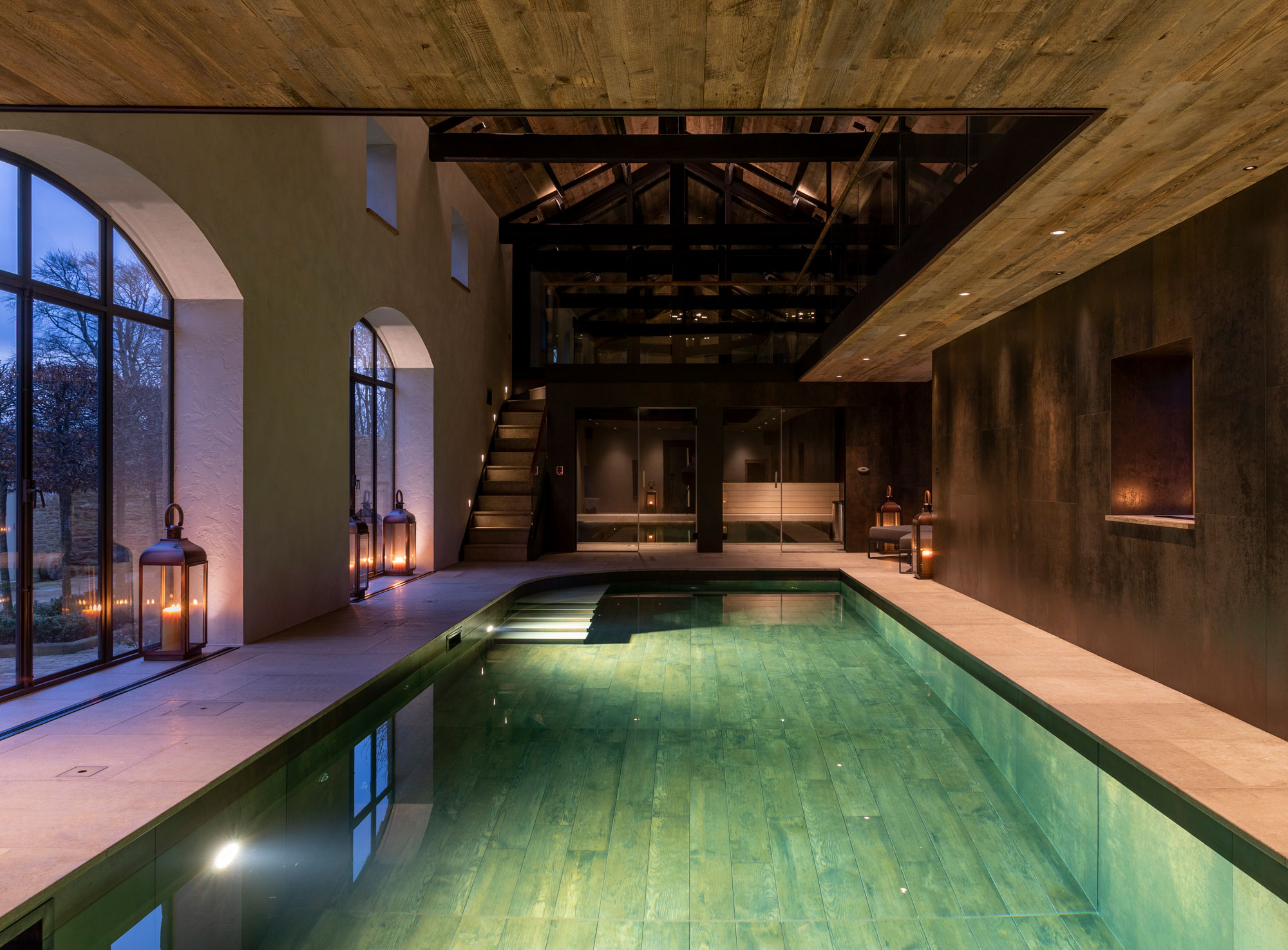 Indoor swimming pool at night with mood lighting and large cream tiles