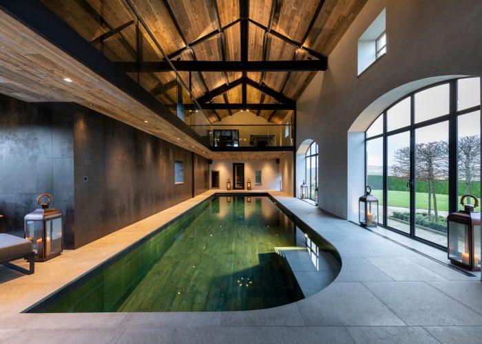 Balcony above indoor swimming pool shining lights on to cream tiled walkway