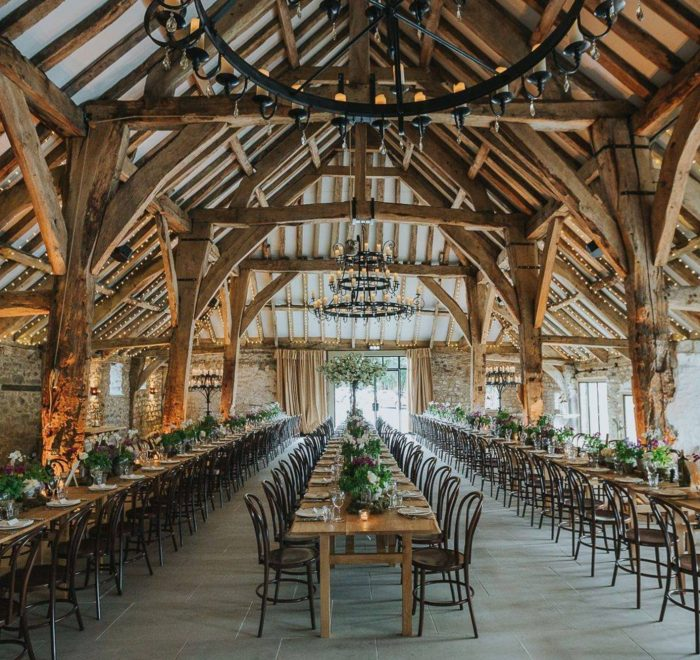 Exposed oak beamed building filled with dining tables and chairs for wedding reception