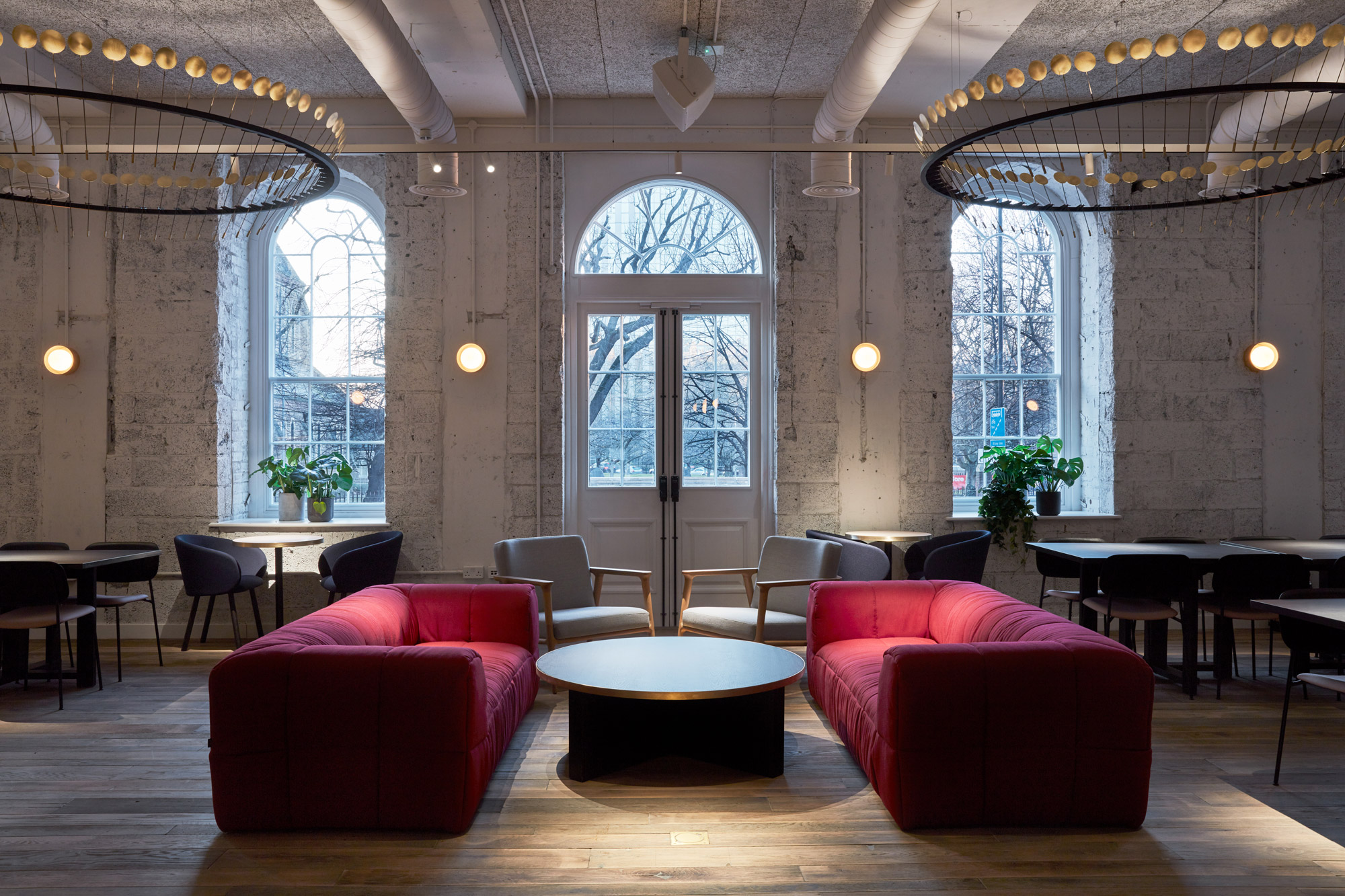 Two red sofas face each other with round coffee table in between and oak floorboards