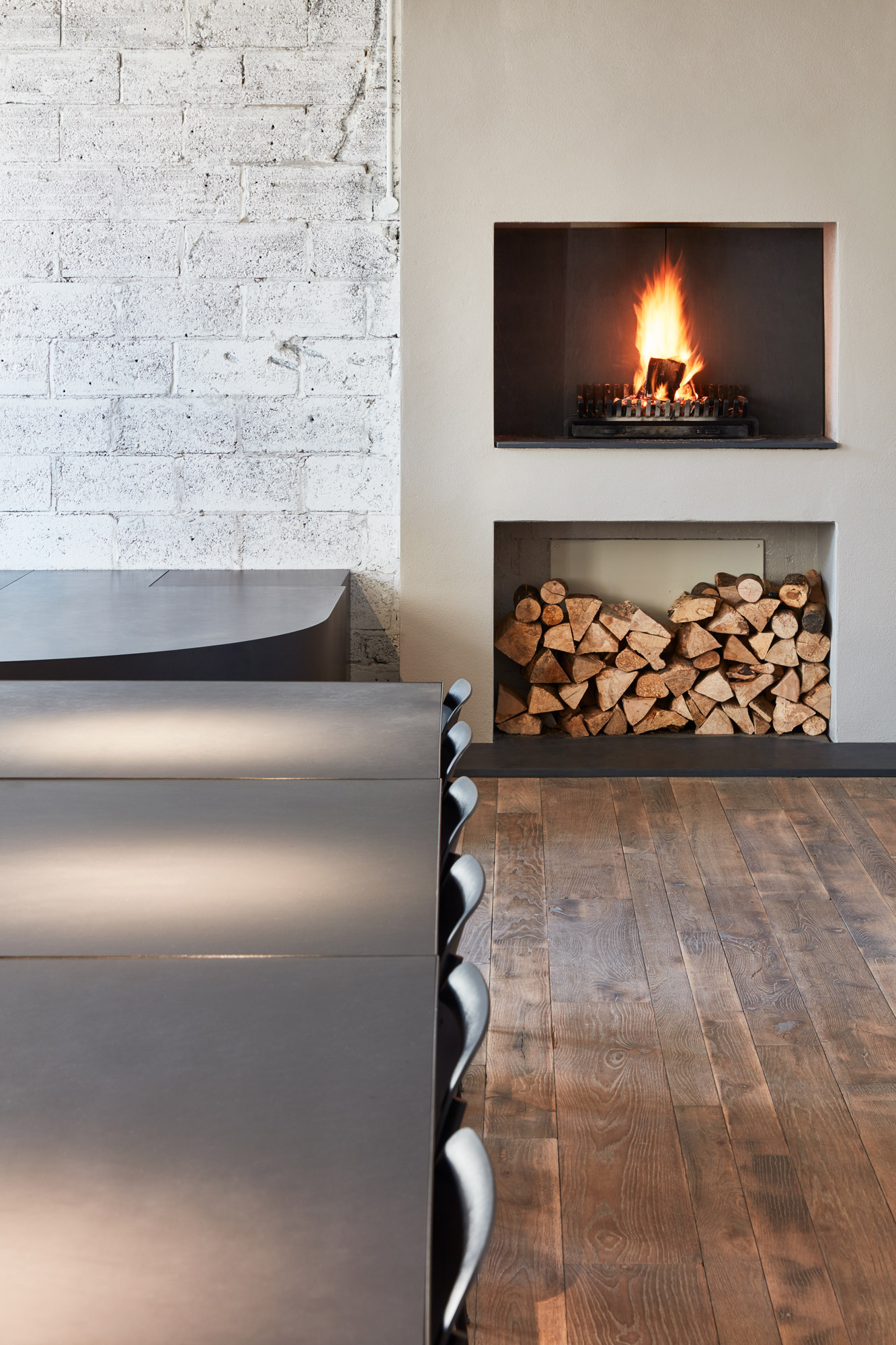 Black dining table with burning fire in background and log storage