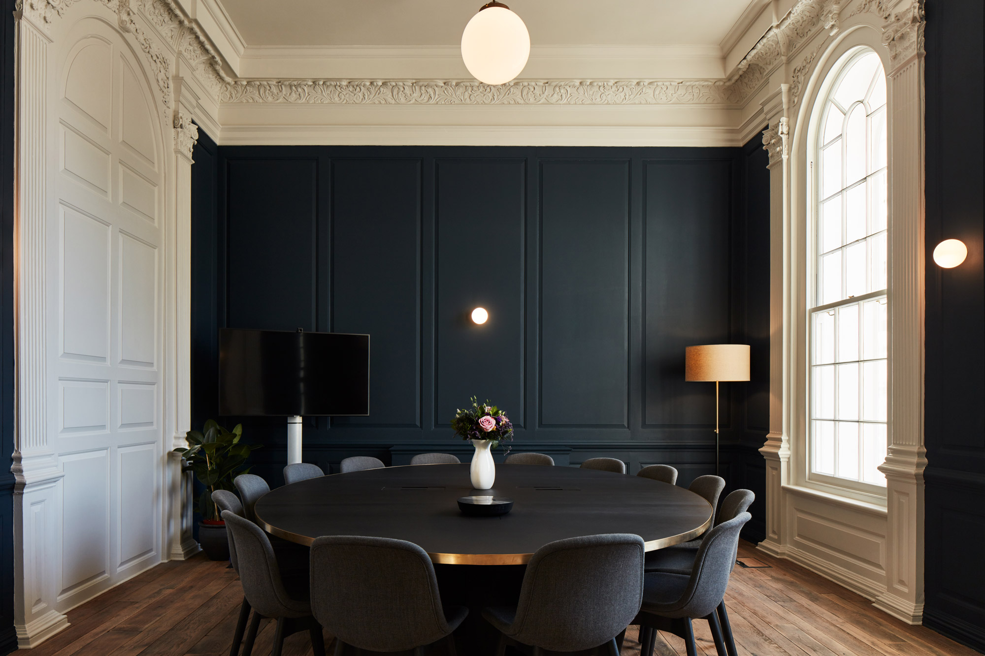 Round dining table with upholstered chairs and painted blue panelled wall