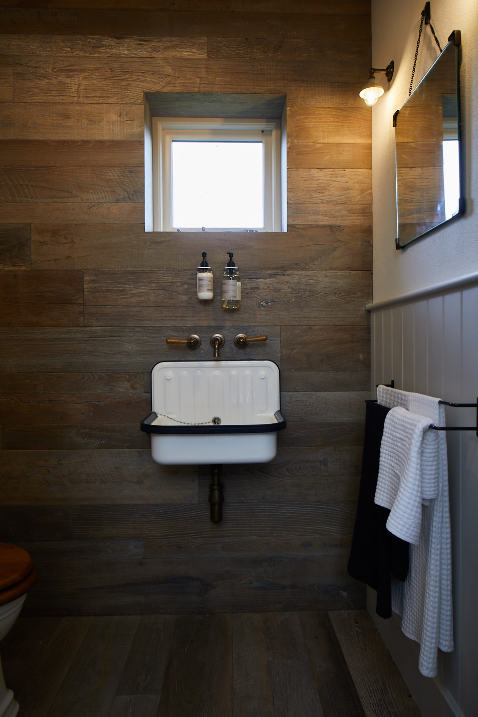 Rustic wood cladding behind sink