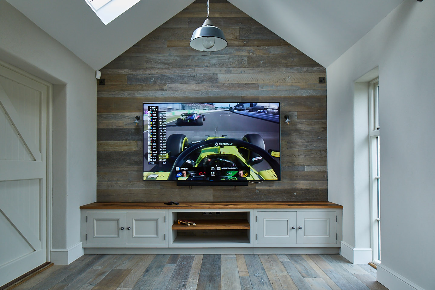High vaulted room with oak cladded wall with tv mounted above low painted unit