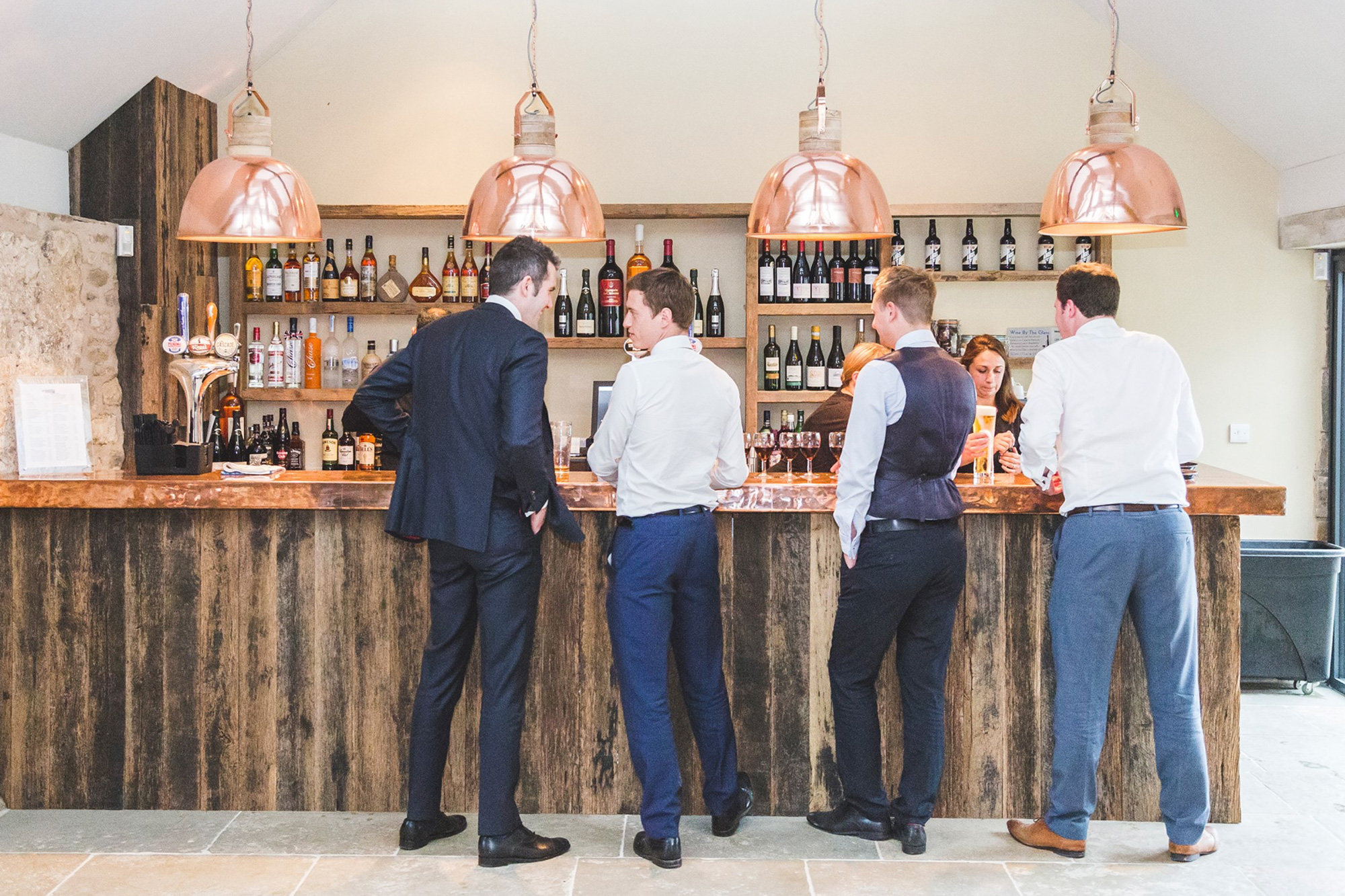Men stood talking at bar with large pendant copper lights