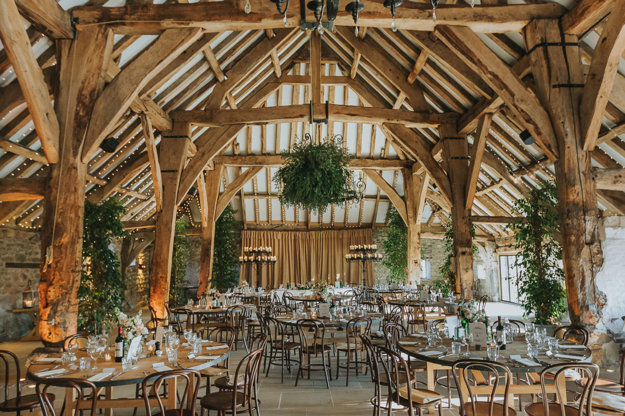 Round dining tables set for wedding reception in large oak beam farmhouse building