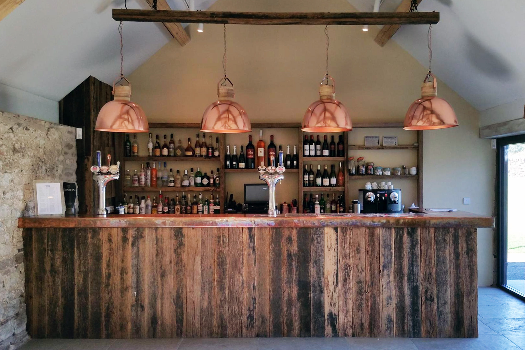 Reclaimed wood bar with large copper pendant lights above
