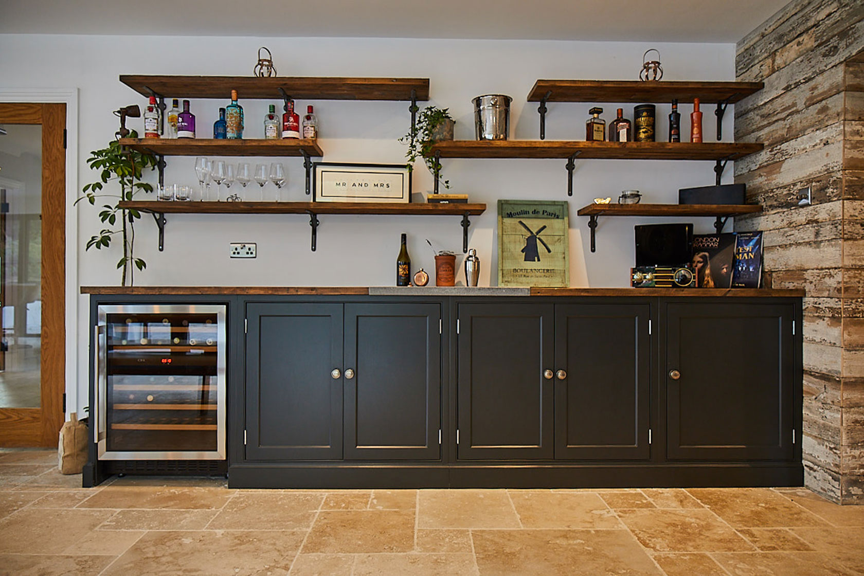Painted blue units with integrated wine cooler and open rustic shelves