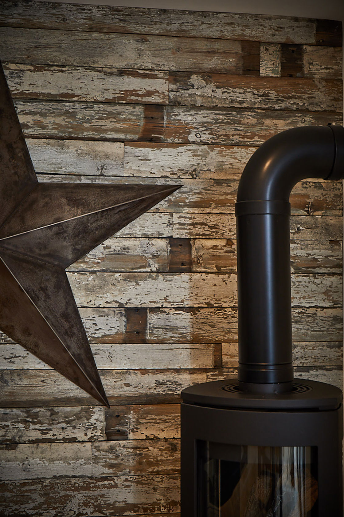 Black log burner with reclaimed rustic wall clad and large metal star