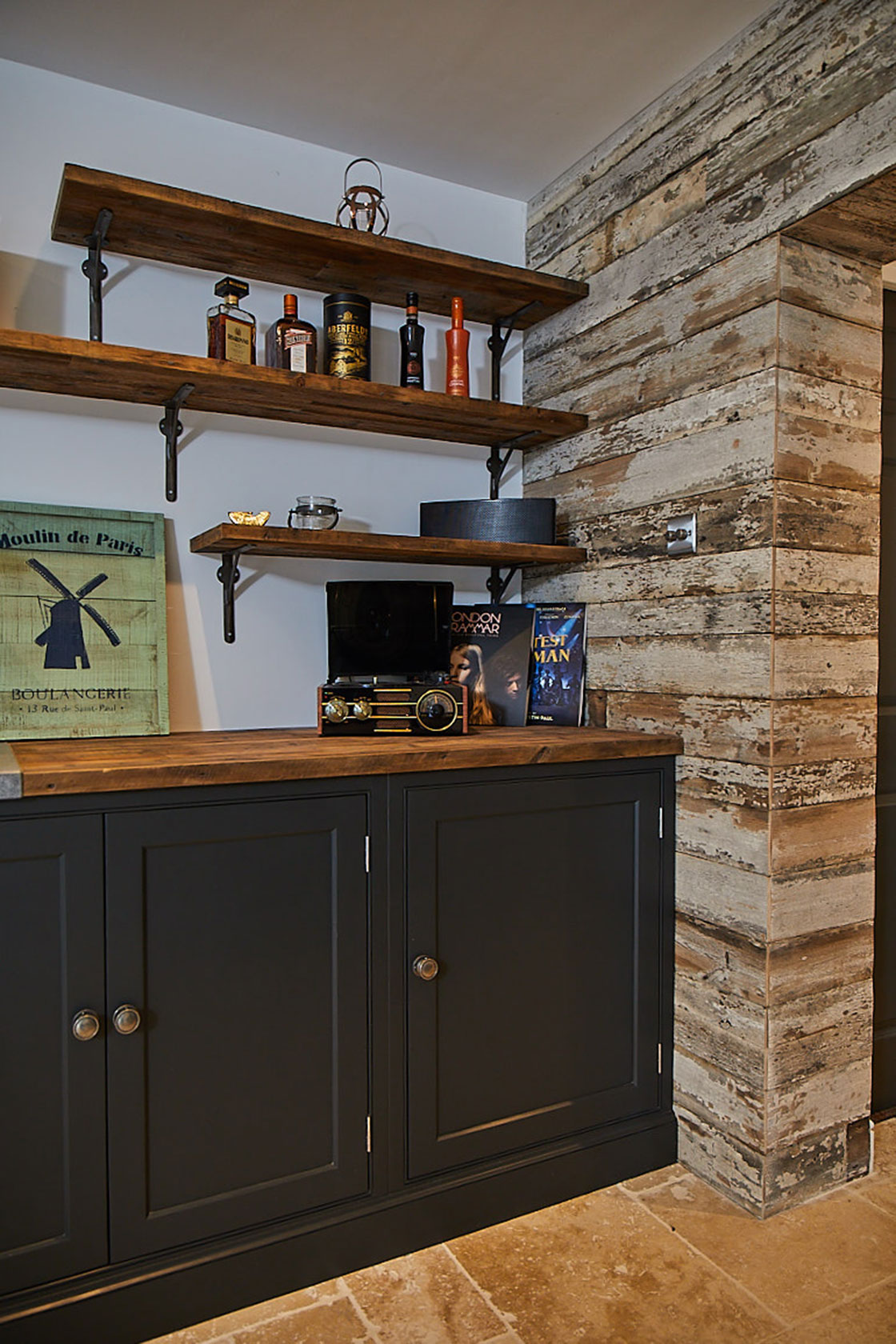 Dark blue bespoke painted units next to crackled white wall cladding and open rustic shelves with cast brackets