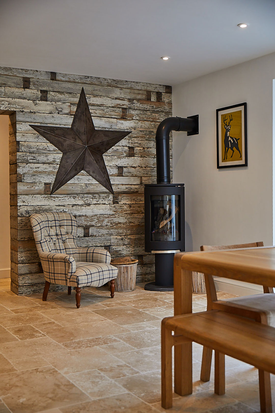 Upholstered occasional chair next to log burning fire and cladded wood wall