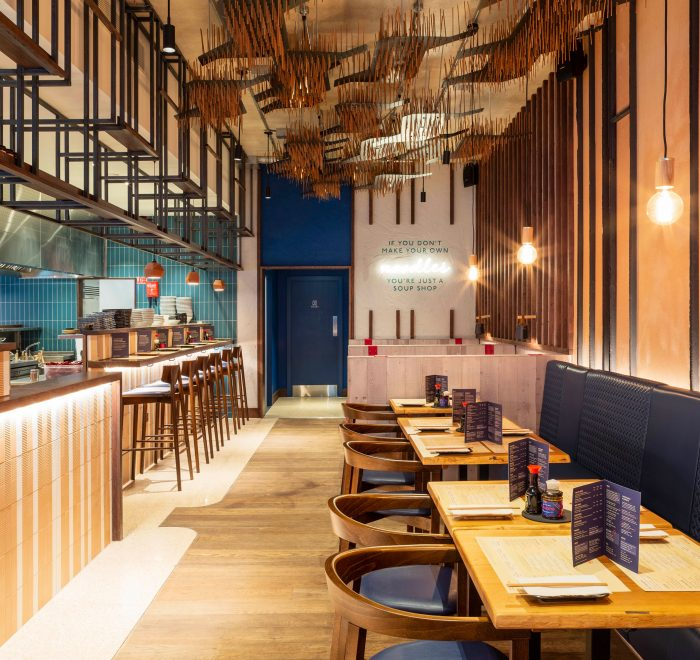 Eatery with blue tiles and walnut and leather blue chairs