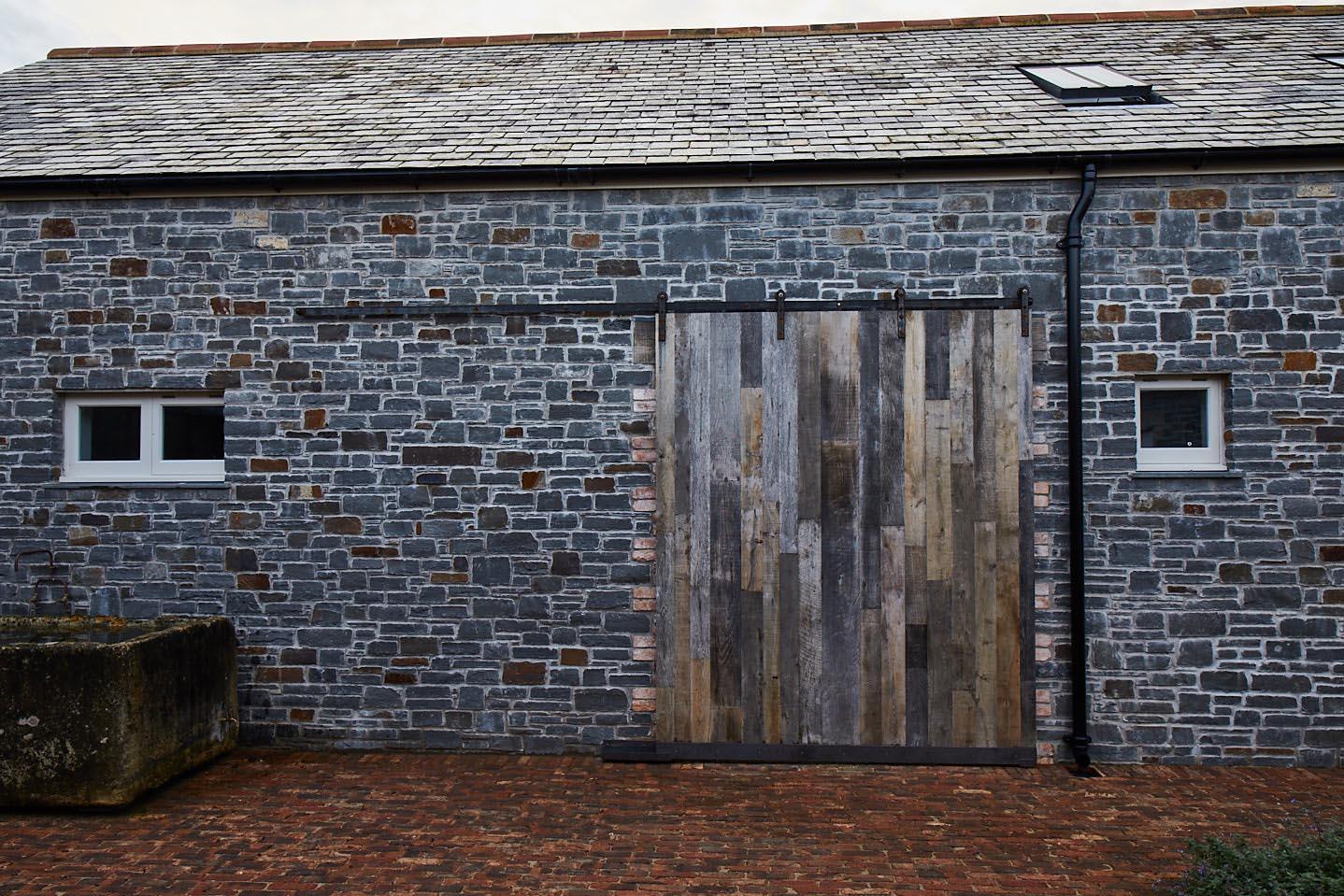 Closed external rustic pine sliding barn door against stone barn