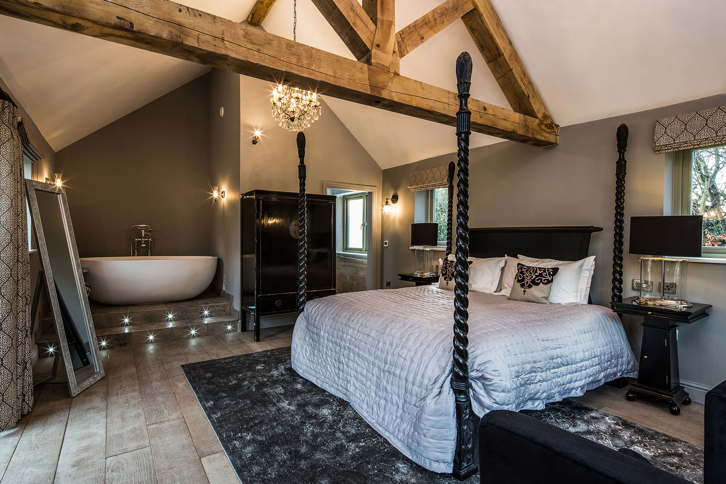 Bedroom with exposed reclaimed beams