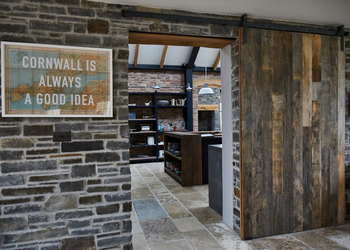 Reclaimed internal sliding barn door against stone wall