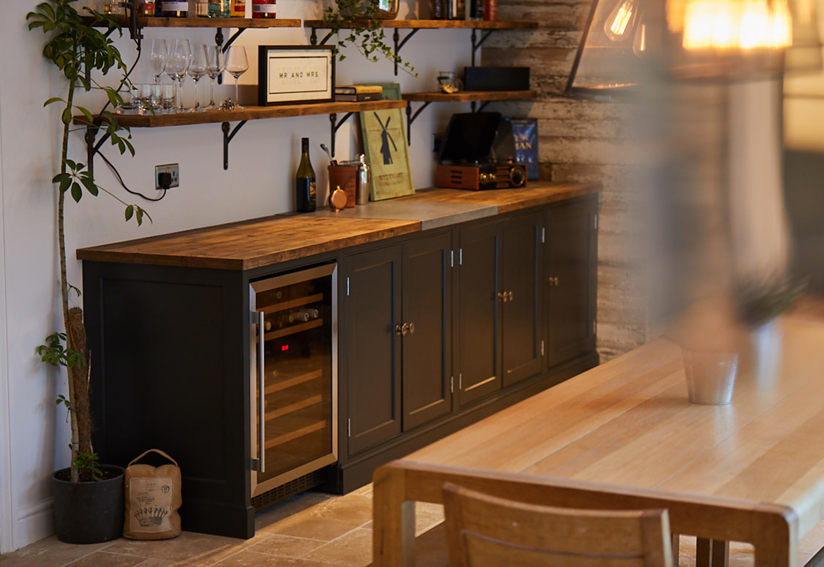 Fitted and integrated wine cooler with dark blue units and reclaimed oak worktop