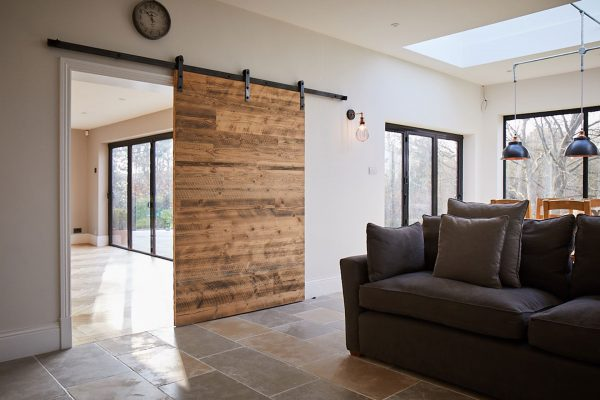 Internal sliding pine door open next to grey sofa with cushions