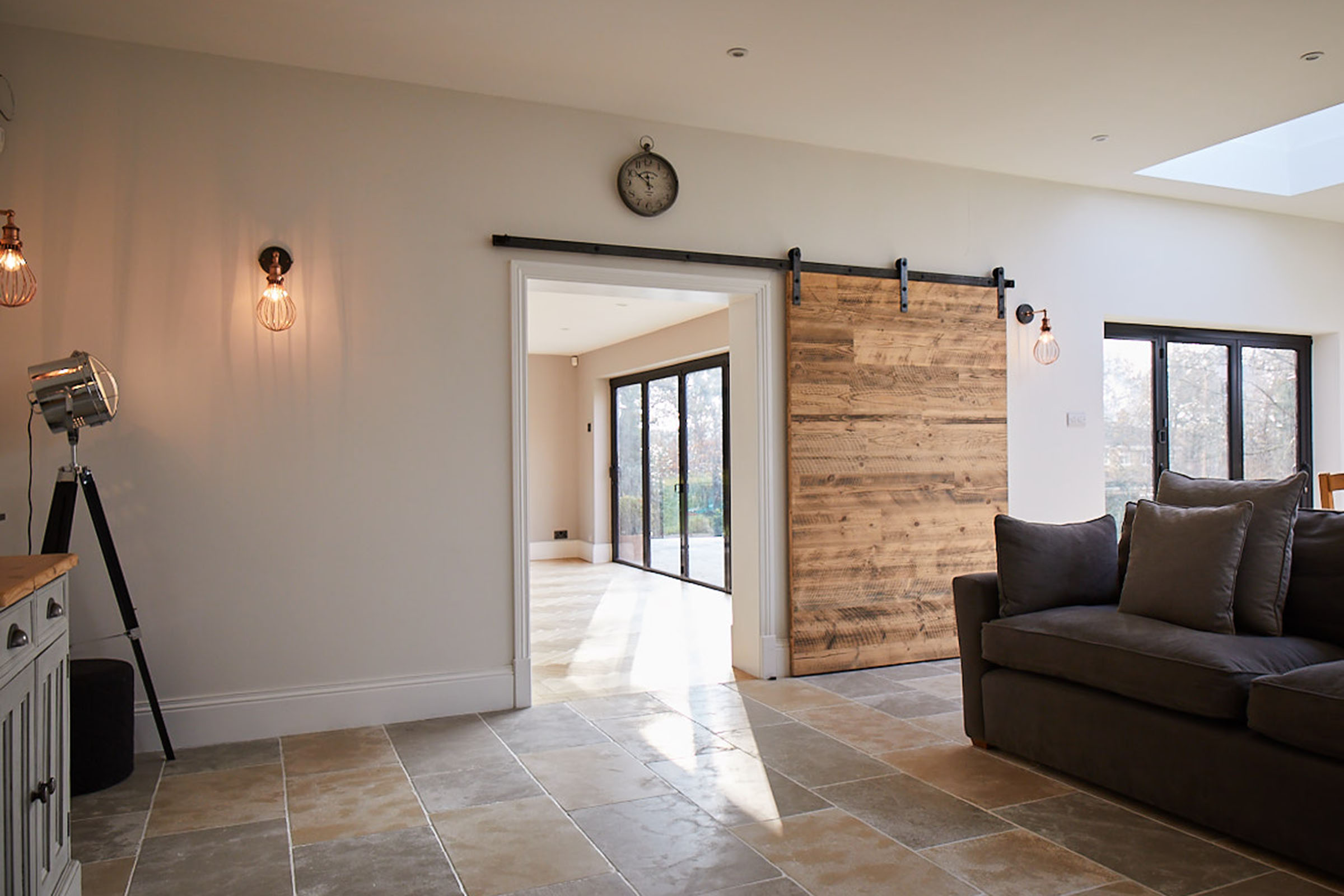 Internal sliding door with raw steel rail next to floor lamp and grey sofa