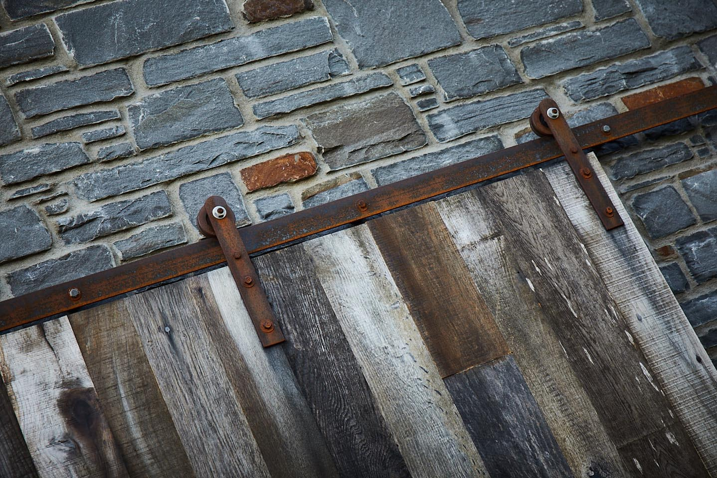 Rusted raw steel sliding door mechanism against stone wall
