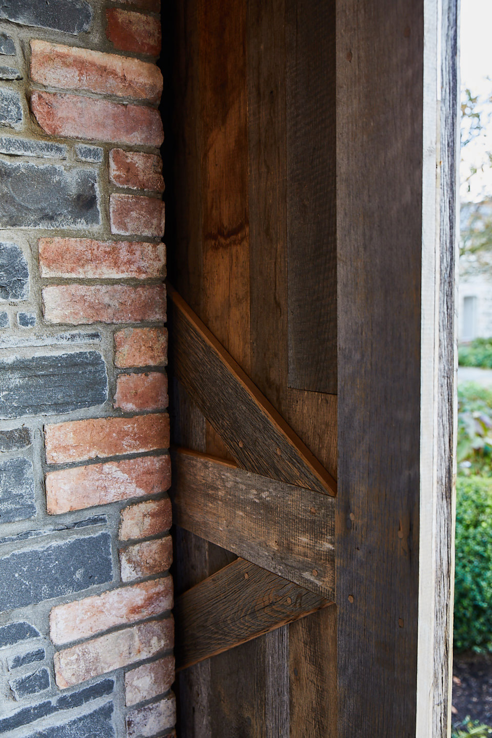 Sliding pine barn door with z detail on the back next to brick wall