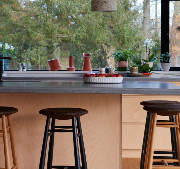Solid oak bar stools sit under solid concrete worktop overhang