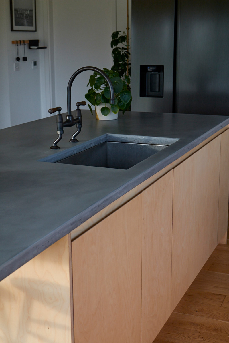 Solid grey concrete worktops on birch plywood sink unit