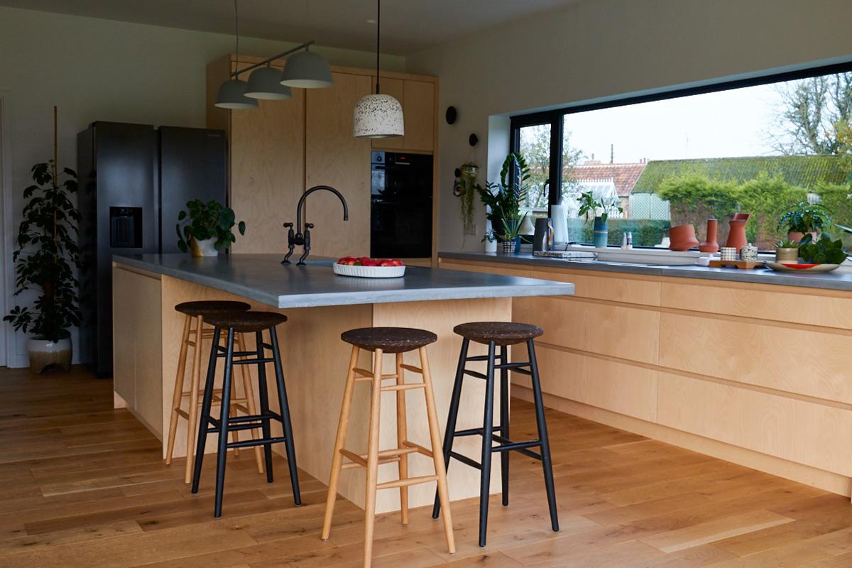 Overhang on kitchen island makes room for oak bar stools