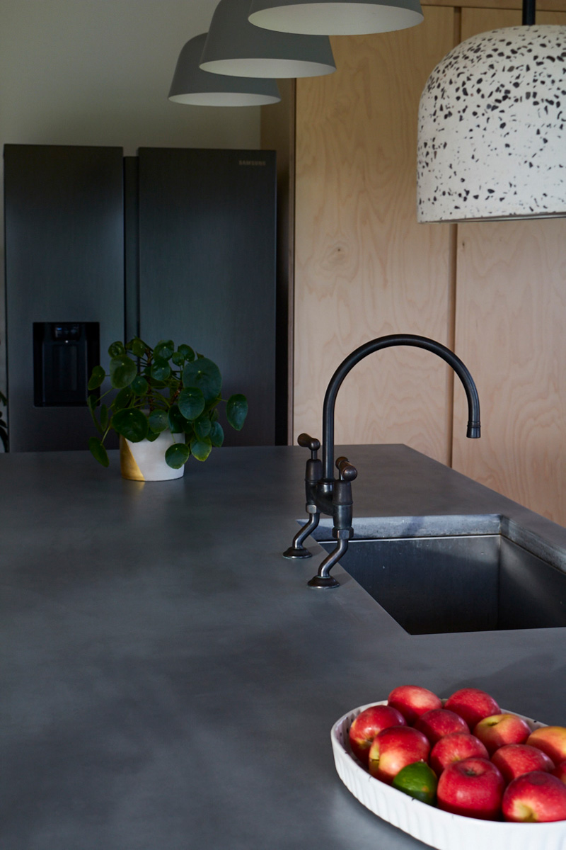 Solid grey concrete worktops with inbuilt sink and antique brass taps