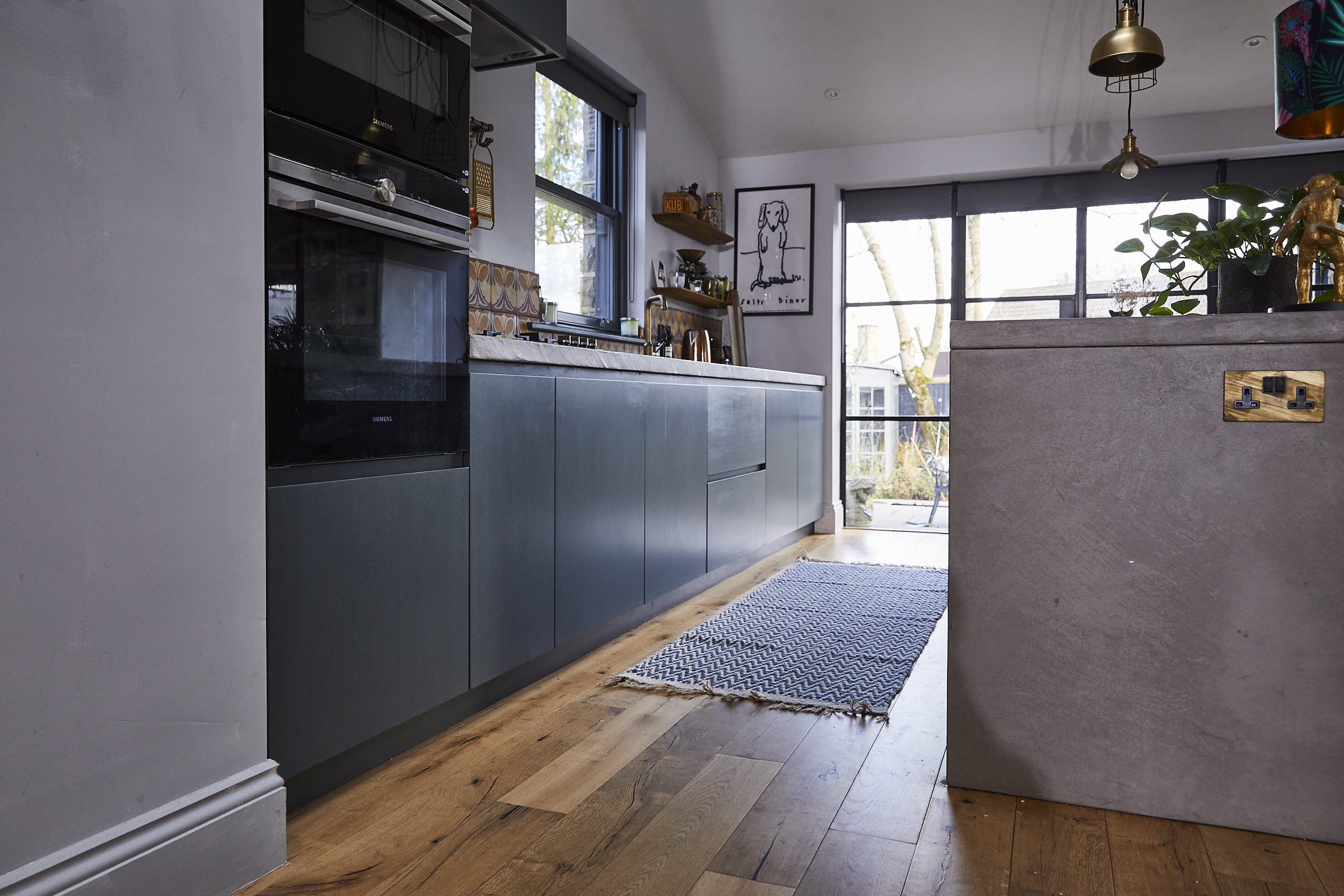 Oak flooring in kitchen with blue and white zig zag rug